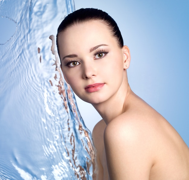 Young beautiful woman with stream of water - blue wall