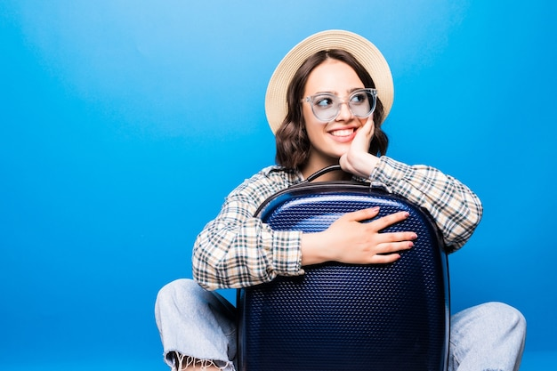 Young beautiful woman with suitcase with sunglasses and straw hat ready for summer trip