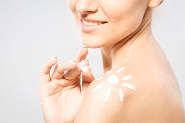 Young beautiful woman with sun-shaped sun cream. pretty woman ready for suntan treatment. sunscreen lotion sun drawing on woman shoulder. isolated on white background. close-up.