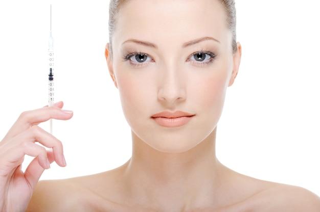 白の手に注射器を持つ若い美しい女性