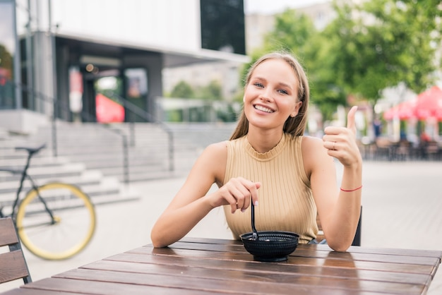 Young beautiful woman with thumbs gesture while eat salad at outdoors cafe