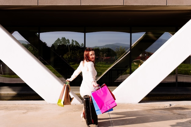 旅行スーツケースとカラフルな買い物袋を持つ若い美しい女性。出張とショッピングのコンセプト