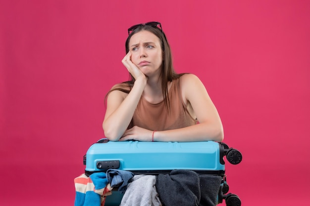 Young beautiful woman with travel suitcase full of clothes looking aside with frowning face displeased and tired thinking standing over pink background