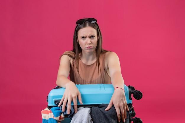 Giovane bella donna con la valigia di viaggio piena di vestiti che guarda l'obbiettivo con il viso accigliato con espressione arrabbiata in piedi su sfondo rosa