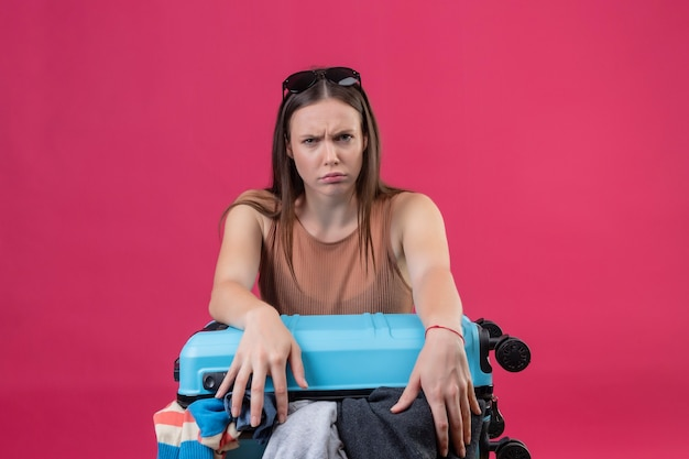 ピンクの背景の上に立って怒っている表情で顔をしかめ顔でカメラ目線の服でいっぱい旅行スーツケースを持つ若い美しい女性