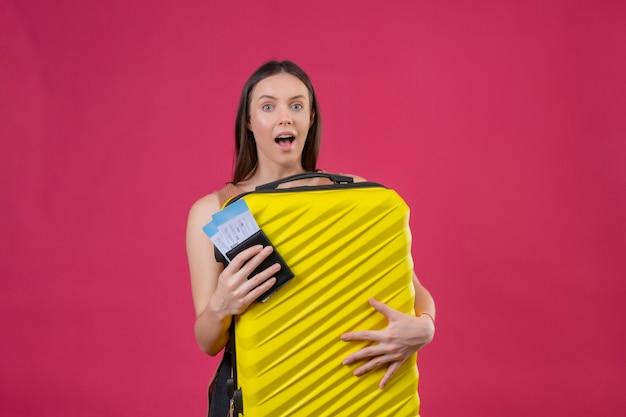 Giovane bella donna con la valigia di viaggio che tiene i biglietti aerei che sembra sorpreso in piedi su sfondo rosa