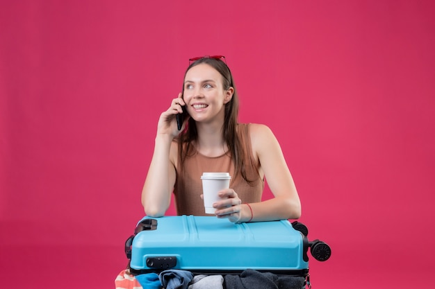 Молодая красивая женщина с чемоданом путешествия, держа чашку кофе, разговаривает по мобильному телефону, улыбаясь на розовой стене