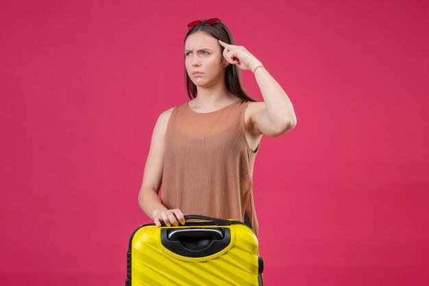 Giovane bella donna con la valigia da viaggio che punta il tempio con il viso accigliato si ricorda di non dimenticare cosa importante in piedi su sfondo rosa