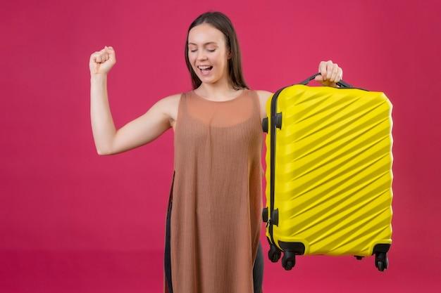 Giovane bella donna con la valigia di viaggio che solleva il pugno dopo una vittoria sorridendo allegramente con il concetto di vincitore faccia felice in piedi su sfondo rosa