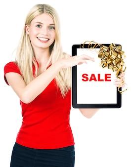 흰색 배경 위에 정의되지 않은 태블릿 pc와 선물 리본 활 장식을 가진 젊은 아름다운 여성. 샘플 텍스트 sale. 크리스마스 쇼핑 개념