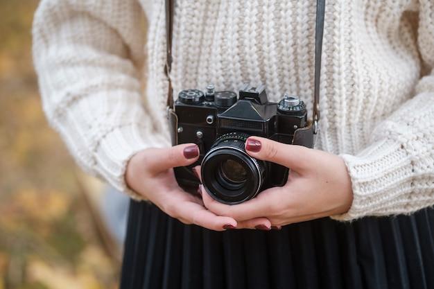 아름 다운가 숲에서 빈티지 카메라와 함께 젊은 아름 다운 여자. 사진 작가는 가을의 아름다움을 포착