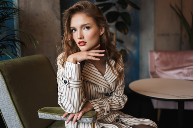 Young beautiful woman with wavy hair in striped trench coat leaning on hand thoughtfully