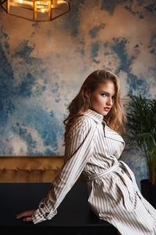 Young beautiful woman with wavy hair in striped trench coat leaning on table thoughtfully