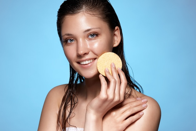 Young and beautiful woman with wet hair cleaning face with sponge