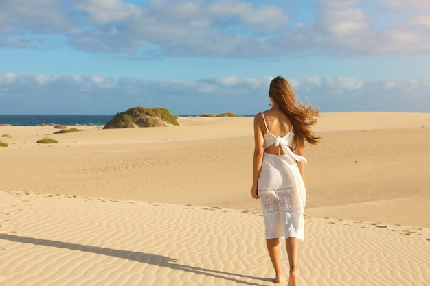 Young beautiful woman with white dress walking on desert dunes at sunset. girl walking on golden sand on corralejo dunas, fuerteventura.