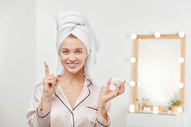 아침 샤워 후 그녀의 얼굴에 보습 크림을 바르려고 머리에 흰 수건을 가진 젊은 아름다운 여자