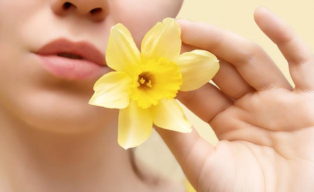 黄色い水仙の花を持つ若い美しい女性をクローズアップ。