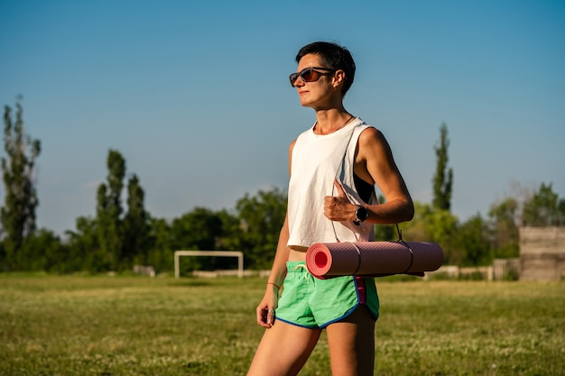 Молодая красивая женщина с ковриком для йоги в парке, короткие черные волосы, солнцезащитные очки и шорты, спорт на открытом воздухе летом, стройная фитнес-девушка в спортивной одежде, женщина на тренировке