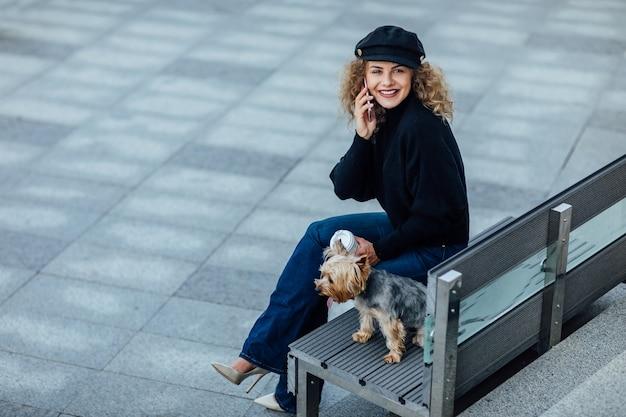 Молодая красивая женщина с йоркширским терьером на фоне зеленого летнего города имеет перерыв. женщина с телефоном.