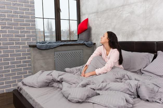 若い美しい女性は、灰色のロフトスタイルで寝室のパジャマを着てベッドに座っている間、目を覚まし、窓の外を見ています