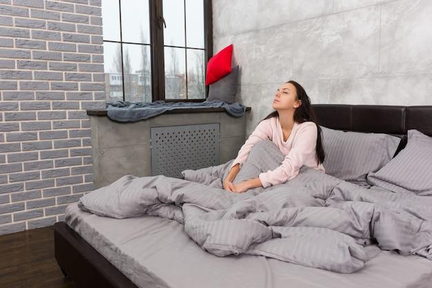 若い美しい女性が目を覚まし、灰色のロフトスタイルで寝室のパジャマを着てベッドに座って