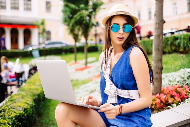 Молодая красивая женщина, работающая на ноутбуке на скамейке на улице