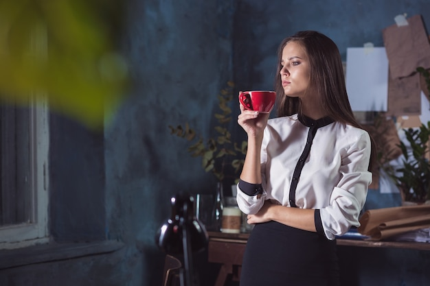 Young beautiful woman working with cup of coffee and notebook at loft office