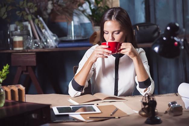 ロフトオフィスでコーヒーとノートブックを操作する若い美しい女性