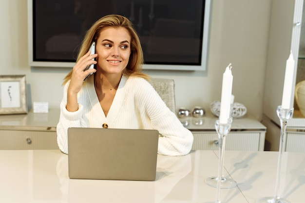 젊은 아름다운 여성은 프리랜서로 흰색 책상에 노트북을 놓고 집에서 컴퓨터를 위해 일합니다. 집에서 일하는 동안 전화 통화를 하는 젊은 사업가.