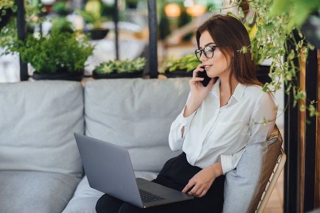 Una giovane e bella donna lavora su un laptop sulla terrazza estiva del suo ufficio moderno e parla al telefono