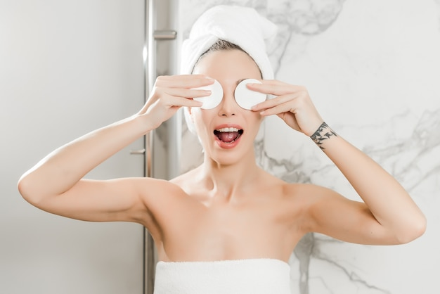 Young beautiful woman wrapped in towels in the bathroom applies cotton pads on eyes