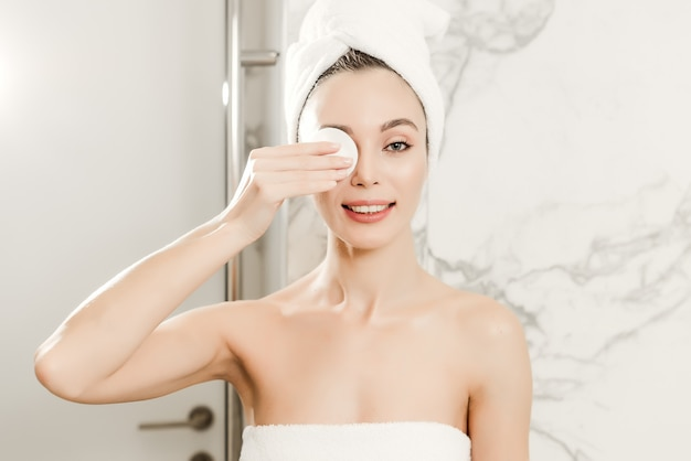 Young beautiful woman wrapped in towels cleans her face with cotton pad in the bathroom