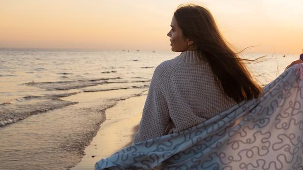 Молодая красивая женщина, закутанная в теплое одеяло, тепло и уютно на пляже. бег по пляжу на закате, чувствуя себя свободным и счастливым