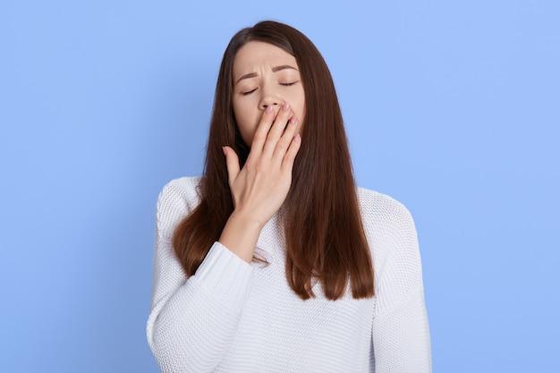 Молодая красивая женщина зевая, показывая усталый жест