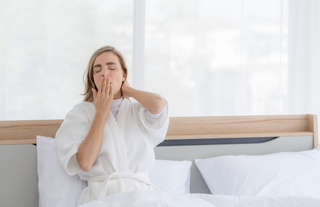 Young beautiful woman yawning while sitting on bed in bedroom at home