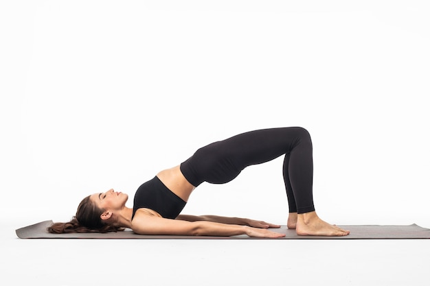 Young beautiful woman yoga posing on isolated white studio surface