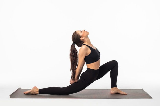 Young beautiful woman yoga posing isolated over white studio surface