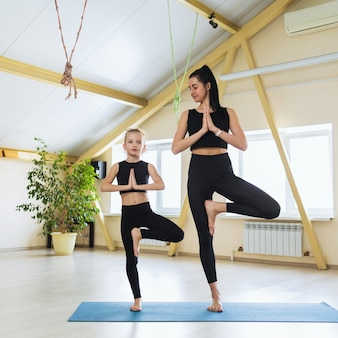 Young beautiful woman yoga trainer and little girl student, perform vrikshasana exercise, tree pose