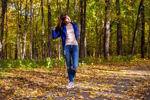 햇빛에 젊은 아름다운 womanin 가을 공원은 노란 나무 배경에 빛난다