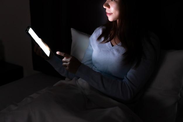 暗い寝室で夜遅くにスマートフォンを使用してベッドで若い美しい女性。携帯電話、インターネット中毒の概念