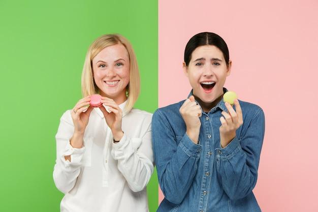 Giovani belle donne che tengono la pasticceria dei maccheroni in sue mani
