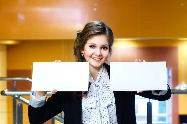 Young beautiful women holding two blank white card