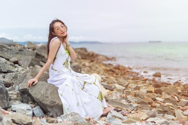 海辺の岩の上の白い座席の若い美しい女性。