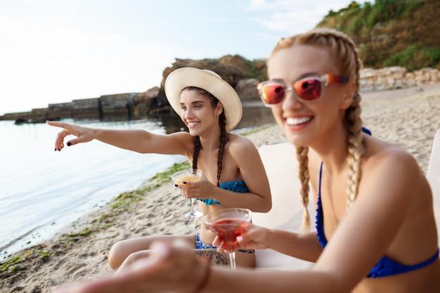 Giovani belle donne che ridono, puntando le dita lontano, sdraiato vicino al mare