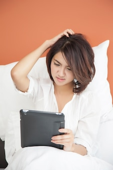 Young beautiful women looking a tablet on bed, acting confuse