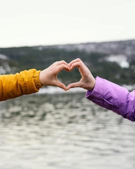Young beautiful women in nature making heart hand shape
