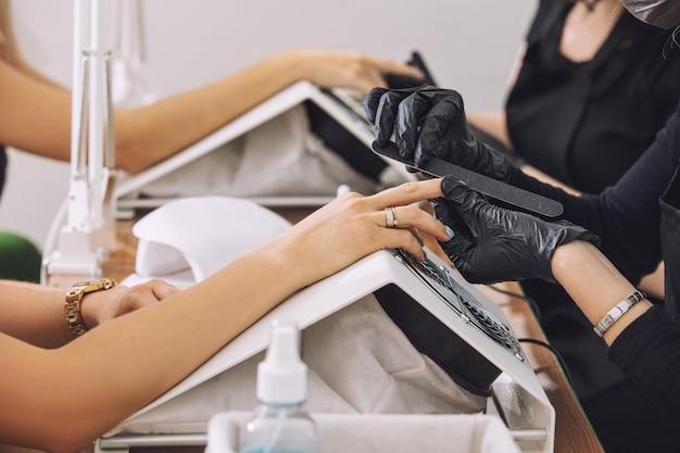 Молодые красивые женщины клиентки делают маникюр у профессиональных мастеров маникюра в салоне красоты Premium Фотографии