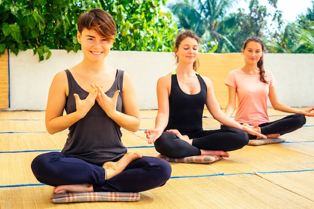 Young beautiful women practice group meditation on yoga class