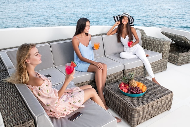 Молодые красивые женщины плывут на яхте