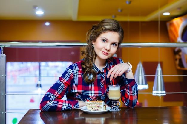 モカチノとケーキのカップとカフェに座っている若い美しい女性